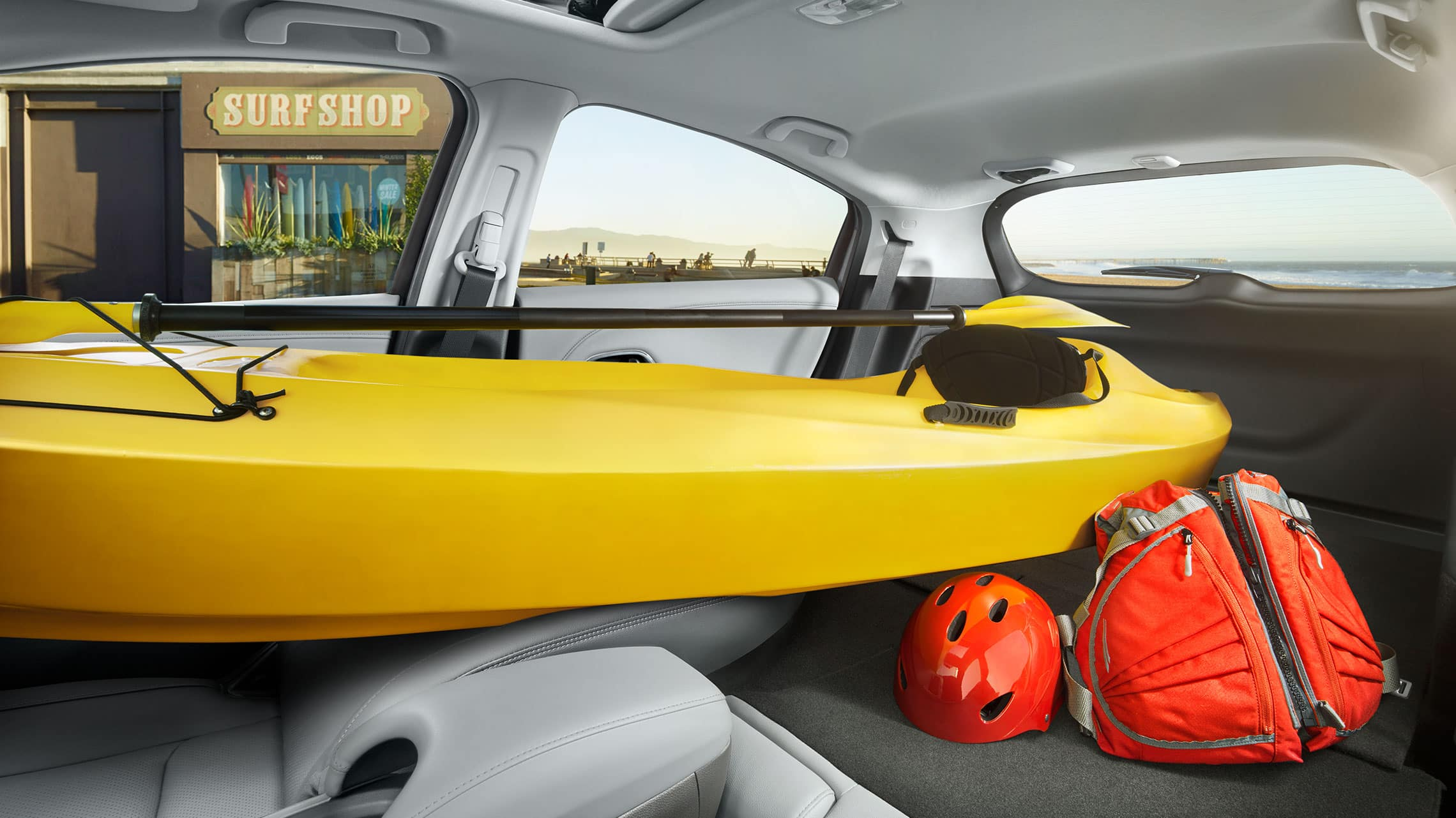 Interior view of the 2019 Honda HR-V Touring in Gray Leather with all rear seats and passenger seat folded down storing a kayak and luggage.