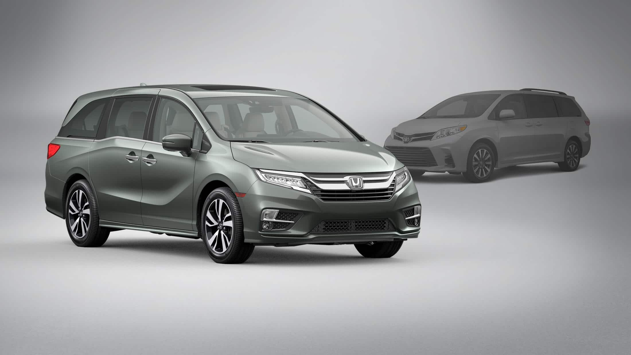 Front 3/4 passenger-side view of 2020 Honda Odyssey in Forest Mist Metallic parked in front of 2020 Toyota Sienna.