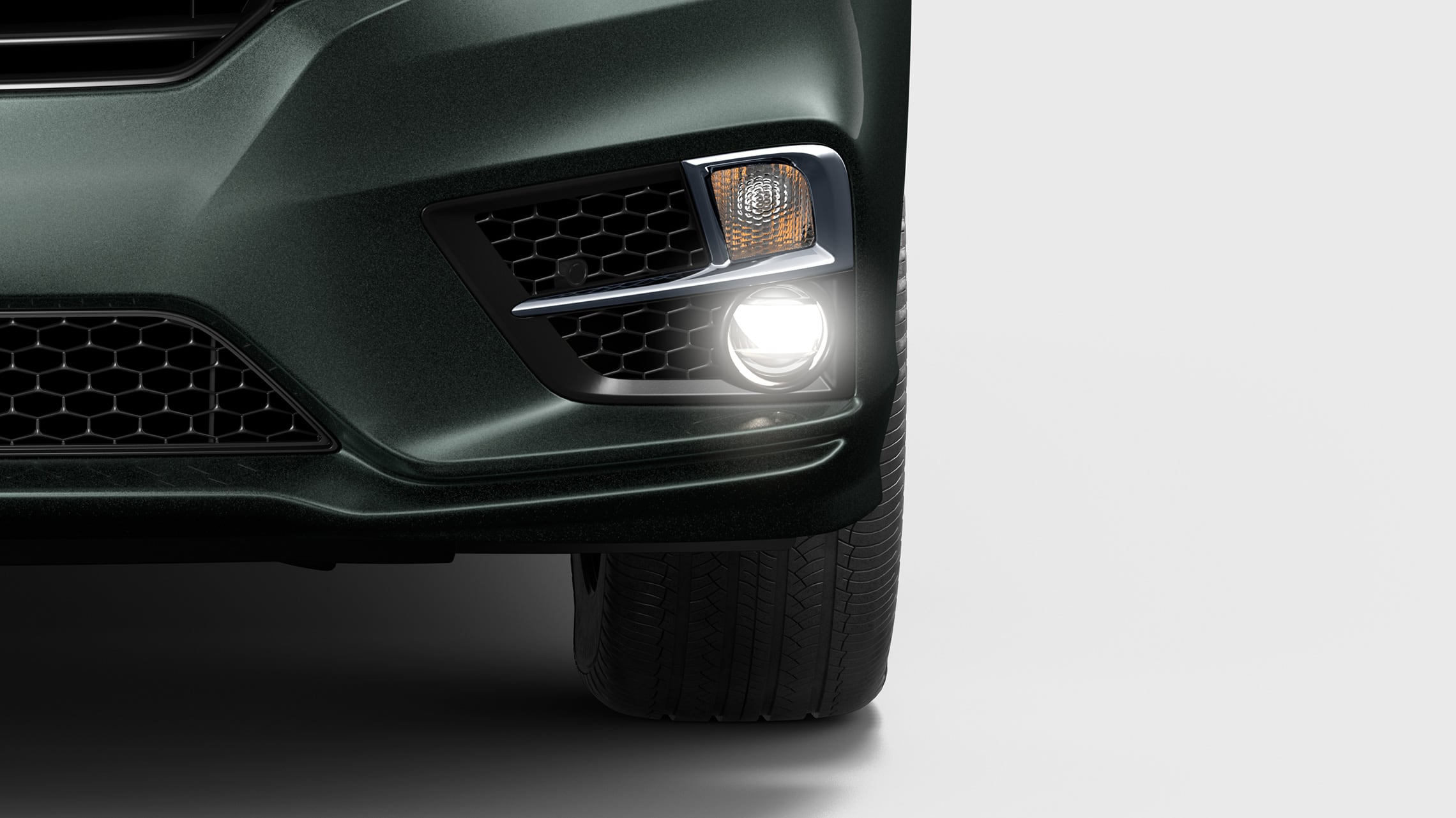 Front close-up view of driver-side headlight on 2020 Honda Odyssey Elite in Forest Mist Metallic.