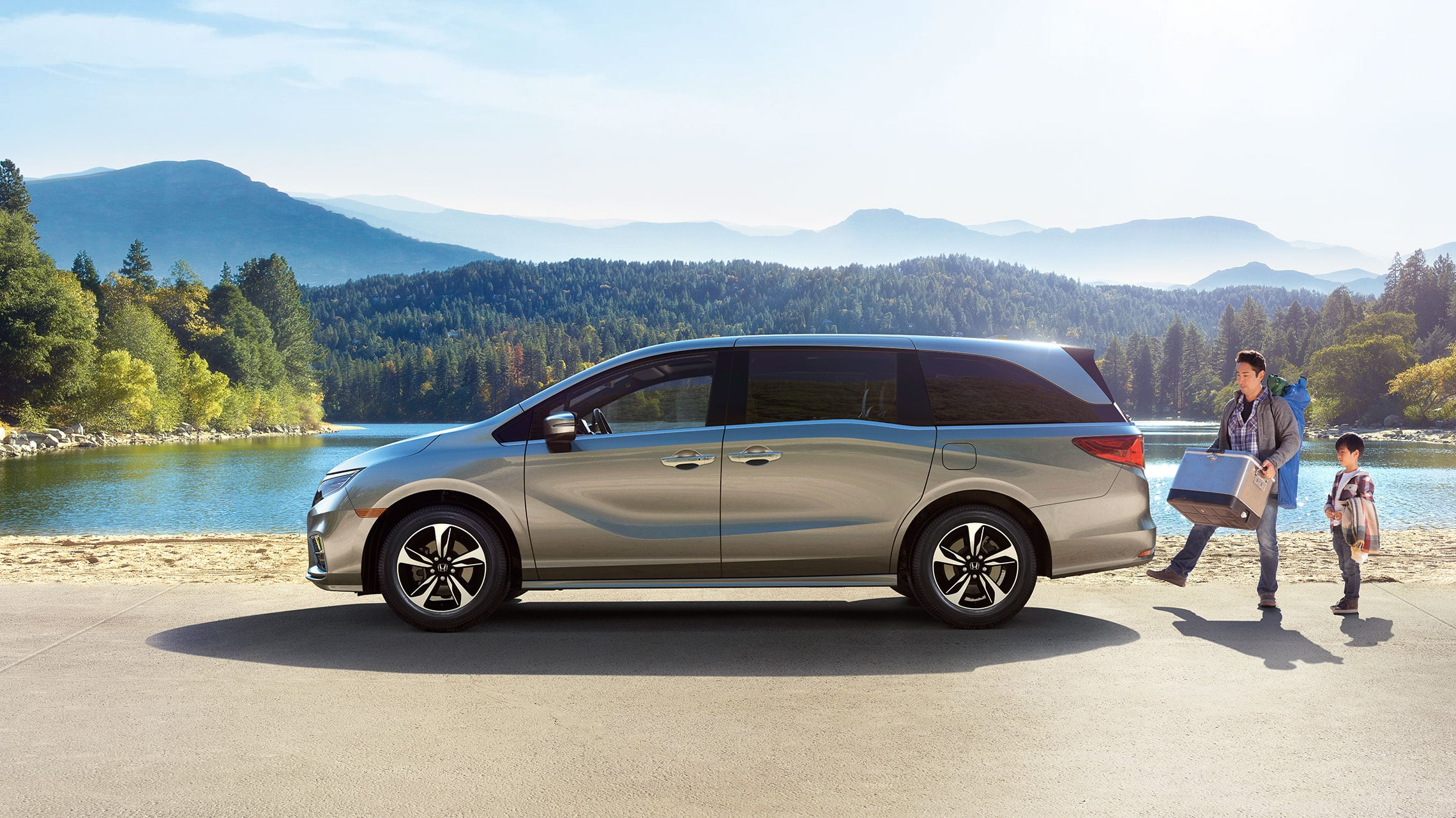 Driver-side profile view of 2020 Honda Odyssey Touring in Lunar Silver Metallic parked in forest environment.