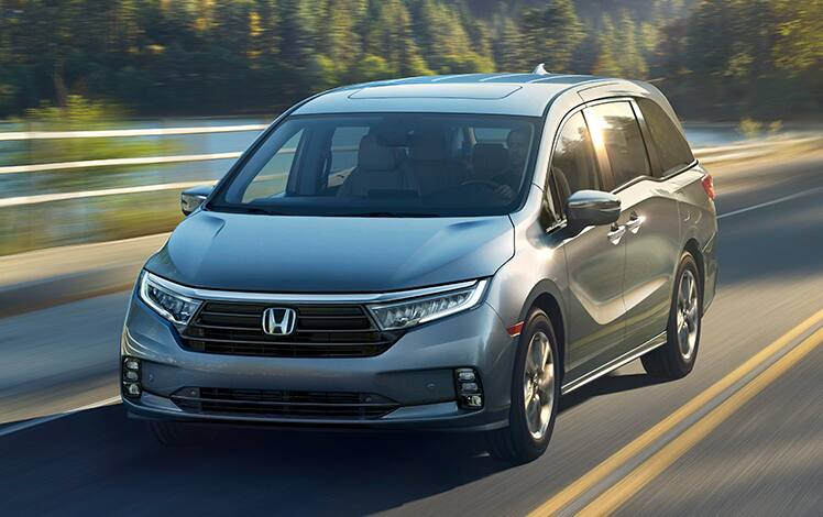Front driver-side view of the 2021 Honda Odyssey Elite in Modern Steel Metallic driving on a mountain road.
