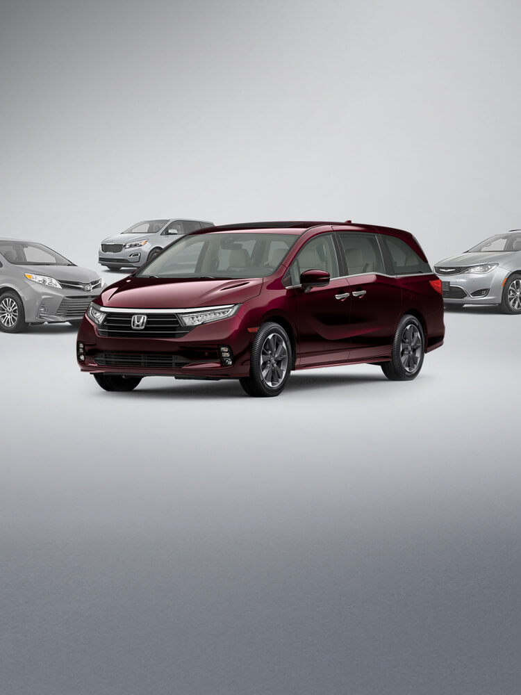 Front driver-side view of the 2021 Honda Odyssey Elite in Deep Scarlet Pearl, with the 2020 Toyota Sienna, 2020 Chrysler Pacifica and 2020 Kia Sedona in the background.